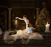 Christmas elf sits on a book with lantern and mouse