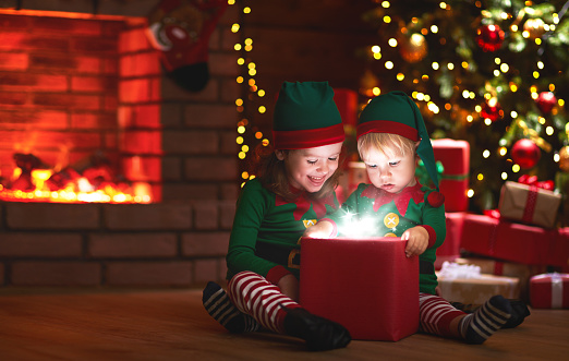 868220646 istock photo Christmas. elves with a magic gift near Christmas tree and fireplace 870898392