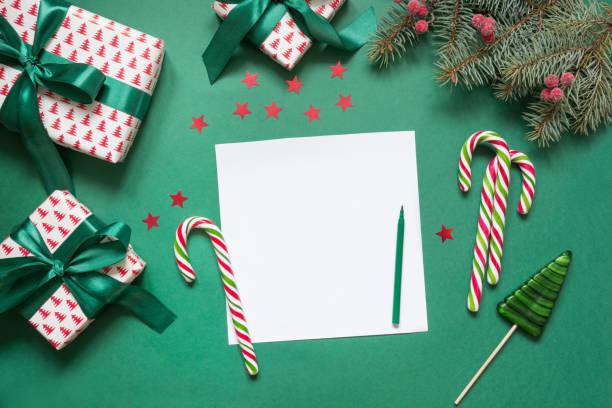 weihnachten leere leere brief an den weihnachtsmann oder einladung auf grün. ansicht von oben. - adventgeschichte stock-fotos und bilder