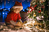 High angle view of girl in red clothes playing by the Christmas tree and waiting for a big surprise to arrrive at midnight.
