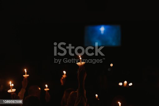 People holding candles and candles by themselves at a Christmas Eve church service or a vigil.