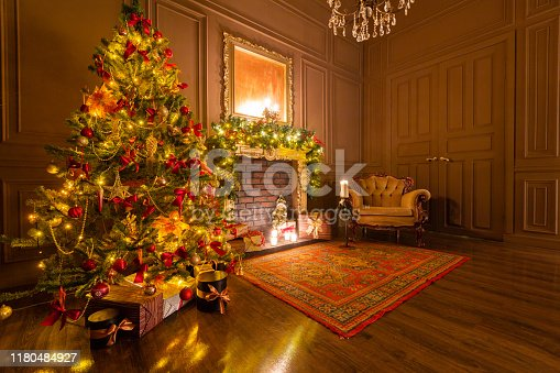 istock Christmas evening by candlelight. classic apartments with a fireplace, decorated tree, armchair. 1180484927