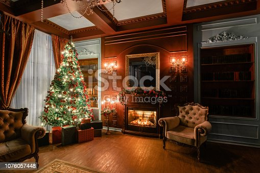 gifts at the Christmas tree. Christmas evening by candlelight. classic apartments with a fireplace