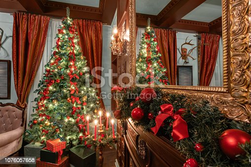 istock Christmas evening. Gifts at the Christmas tree. Classic apartments with a fireplace. Room with shelves of books 1076057658
