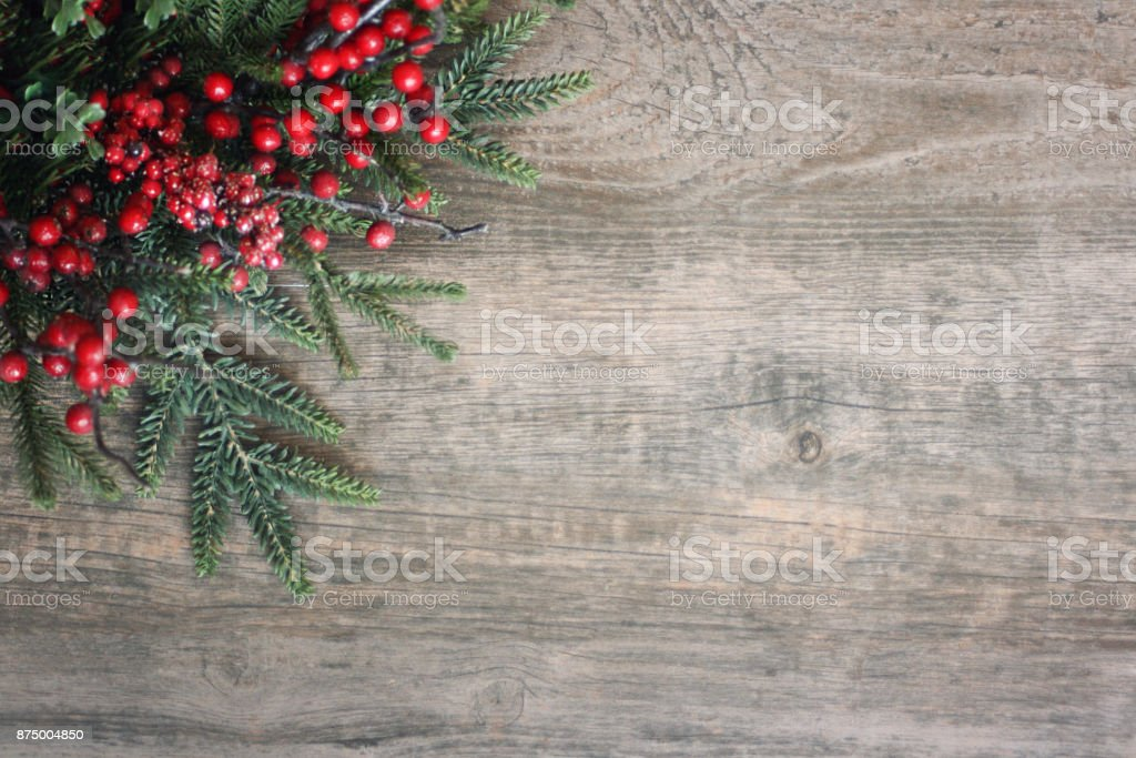 Christmas Evergreen Branches and Berries in Corner Over Wood stock photo