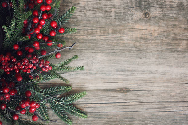 Christmas Evergreen Branches and Berries Over Wood Christmas Evergreen Branches and Berries Over Rustic Wood Background evergreen tree stock pictures, royalty-free photos & images