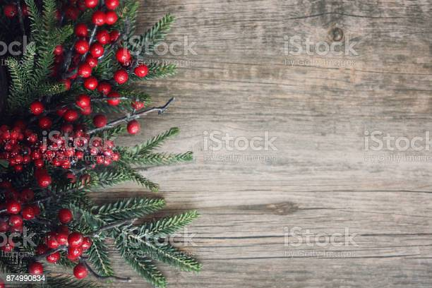 Photo of Christmas Evergreen Branches and Berries Over Wood