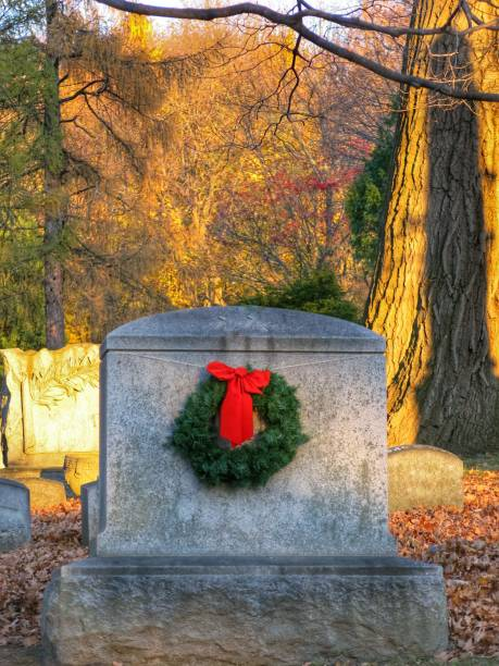 Christmas Evergreen Wreath Placed on Cemetery Grave Tombstone, Fall Foliage stock photo