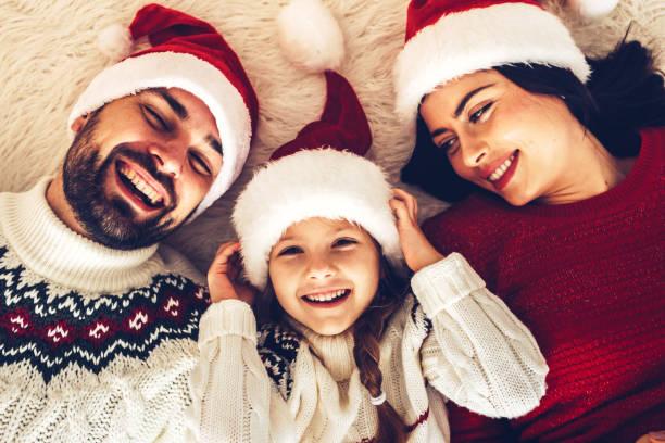 weihnachten-familie! glückliche mama, papa und töchterchen auf santa claus hüte hinlegen. meditieren liebe umarmt, urlaub menschen. zweisamkeit-konzept - weihnachten 7 jährige stock-fotos und bilder