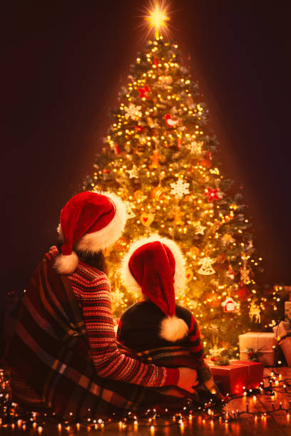 Christmas Family Looking Lighting Xmas Tree, Mother and Child in Red Santa Hats, New Year Night stock photo