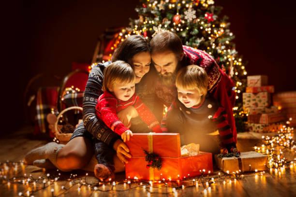 kerst familie open verlichting aanwezig geschenkdoos onder de kerstboom, gelukkige moeder vader kinderen - christmas family stockfoto's en -beelden