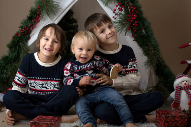 Retrato de familia de Navidad de los hermanos, sentados en decoración para tienda de Navidad con brances, flores, muñeco de nieve, sonriendo y abrazando a - foto de stock
