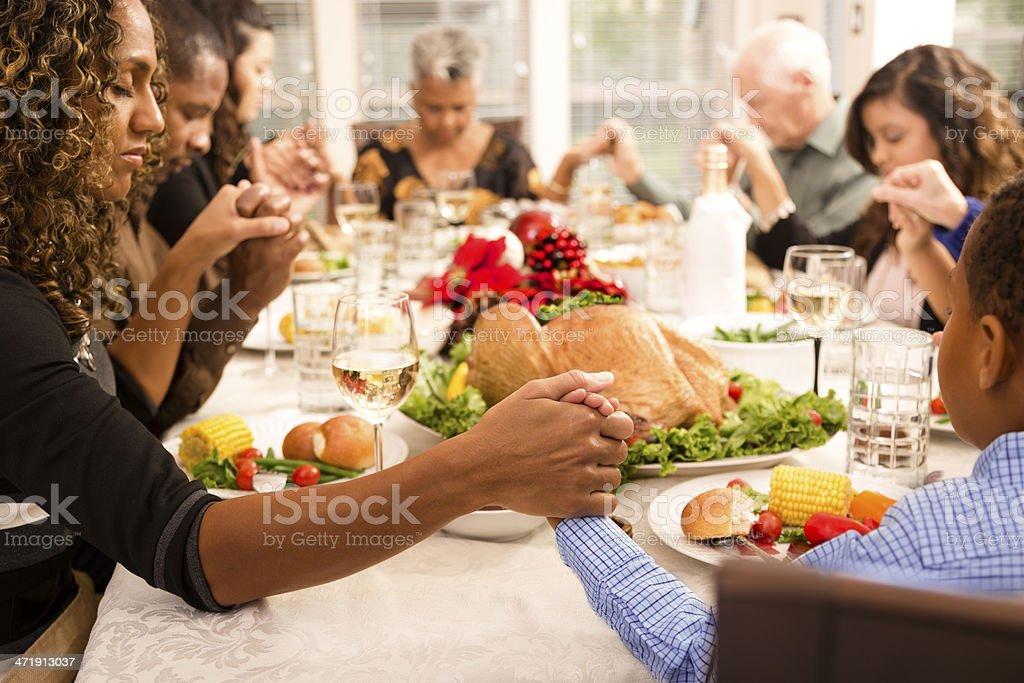 Christmas:  Family prays before eating holiday dinner. stock photo