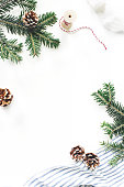 istock Christmas festive composition. Decorative floral frame. Fir tree branches border. Pine cones, gift rope, ribbon and linen cloth on white table background. Flat lay, top view. Copy space, vertical. 1055990008