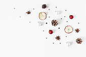 Christmas festive composition. Decorative pattern. Red Christmas balls, baubles, pine cones, dried apple fruit, anise and silver confetti stars isolated on white wooden background, flat lay, top view