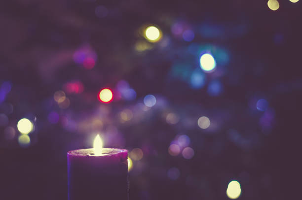 christmas festive concept with christmas tree lights and burning candle