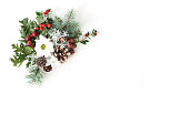 istock Christmas festive floral composition. Pine cones, fir, tree branches, oak leaves, red rowan berries and chrysanthemum flowers on white table background. Decorative corner. Flat lay, top view. 1048231362