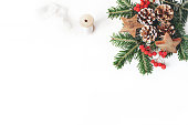 istock Christmas festive styled composition. Decorative banner. Pine cones, fir tree branches, red rowan berries, wooden stars and silk ribbon on white table background. Negative space. Flat lay, top view. 1063391312