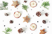 Christmas festive styled composition. Decorative pattern. Pine cones, dried apple fruit, cypress branches, anise, confetti and wooden stars isolated on white wooden background, flat lay, top view