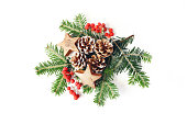 istock Christmas festive styled composition. Winter floral arrangement. Pine cones, fir tree branches, red rowan berries and wooden stars and on white table background. Flat lay, top view. 1066479152