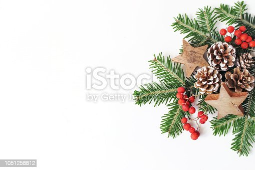 Christmas festive styled floral composition. Pine cones, fir tree branches, red rowan berries and wooden stars on white table background. Decorative frame, web banner, flat lay, top view. Copy space.