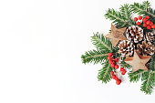 istock Christmas festive styled floral composition. Pine cones, fir tree branches, red rowan berries and wooden stars on white table background. Decorative frame, web banner. Flat lay, top view. Copy space. 1051258812