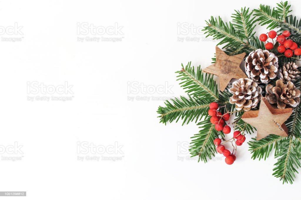 Kerst feestelijke gestileerde florale samenstelling. Dennenappels, fir boomtakken, rode rowan bessen en houten sterren op witte tabelachtergrond. Decoratief frame, webbanner. Plat lag, top uitzicht. Kopieer ruimte. foto