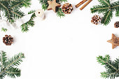 istock Christmas festive styled stock composition. Decorative floral frame. Fir tree branches border. Pine cones, wooden stars, cinnamon and ribbon on white wooden background. Flat lay, top view. Copy space. 1051258828
