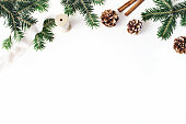 istock Christmas festive styled stock composition. Fir tree branches border. Pine cones, cinnamon and silk ribbon on white wooden background. Flat lay, top view. Copy space. Decorative floral web banner. 1063391262