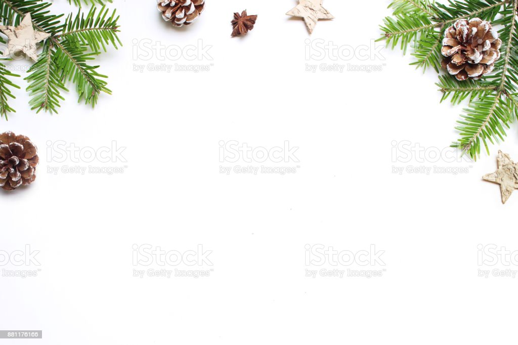 Christmas festive styled stock image. Floral frame composition with pine cones, fir tree branches, wooden and anise stars on white wooden background. Flat lay, top view with empty copy space stock photo