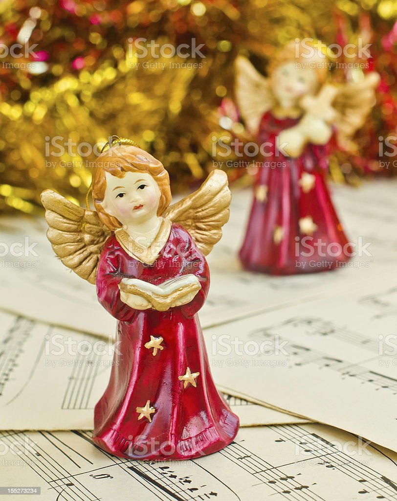 Christmas figurine of angels on a music sheet stock photo