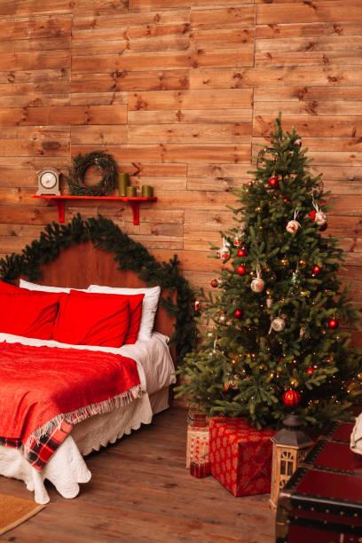 weihnachten tanne und das bett. neujahr-interieur der zimmer mit bett und weihnachtsbaum. - moderner dekor für ferienhaus stock-fotos und bilder