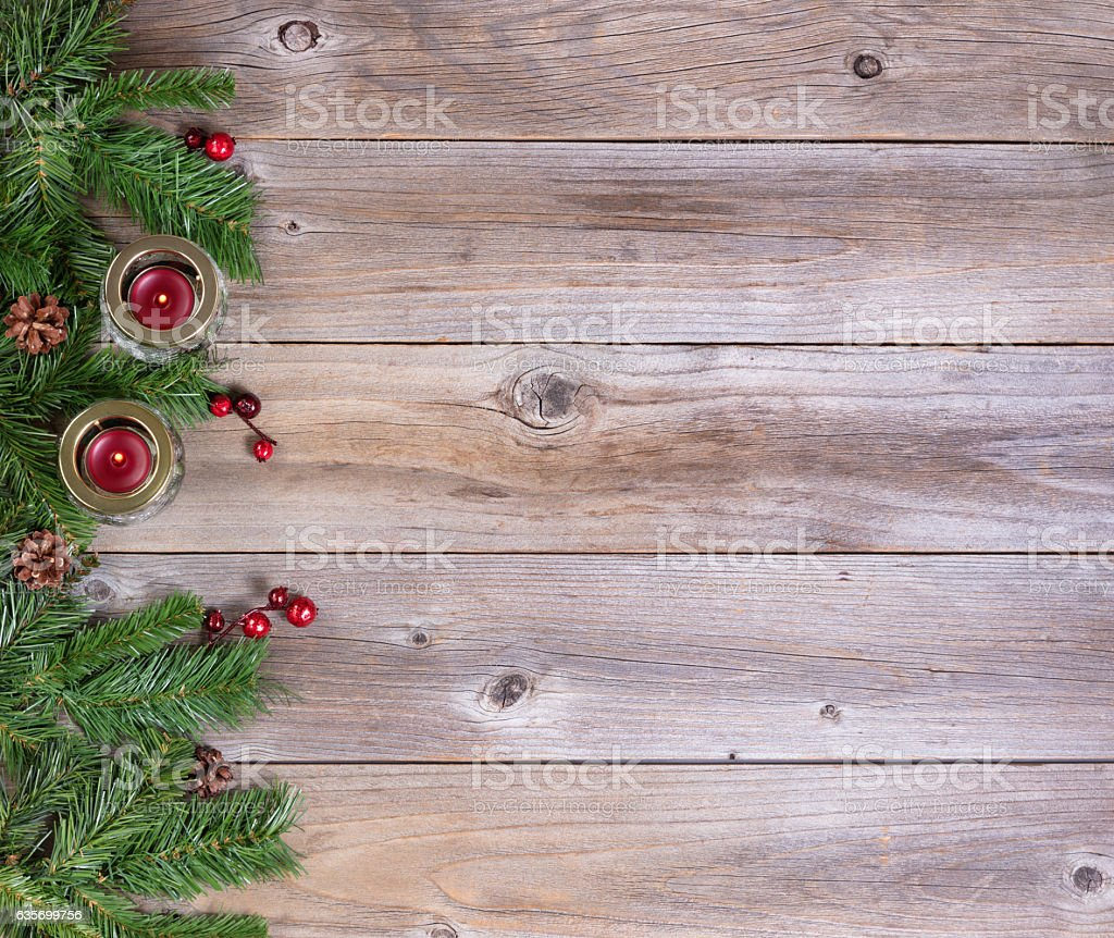 Christmas fir branches and candles on rustic wooden boards royalty-free stock photo