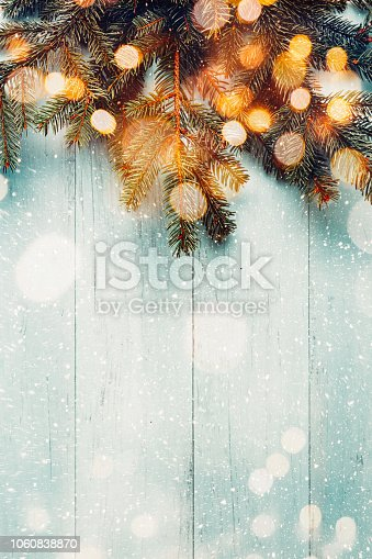 Fir branches on blue wooden planks with lights bokeh. Copy space