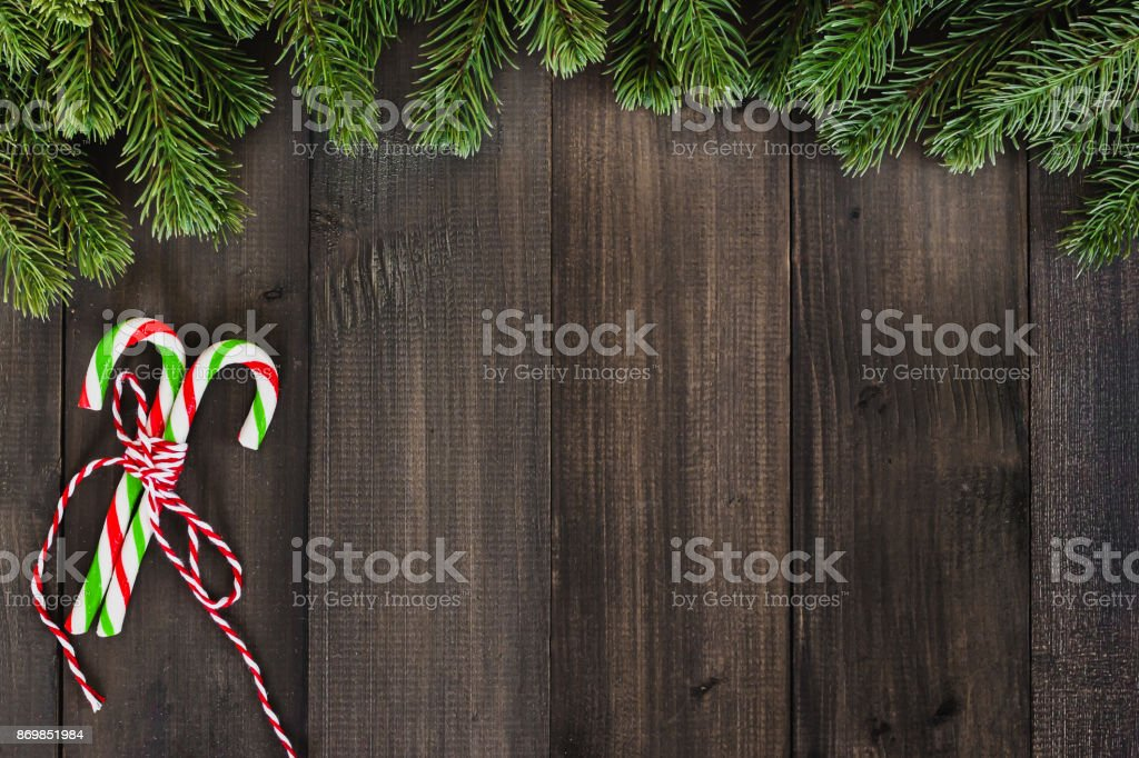 christmas fir tree branches with candy cane ornaments on dark rustic wooden background with copy space