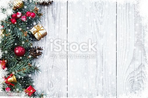 Christmas fir tree branches with toys on old wooden table with bokeh light. Beautiful Christmas background.