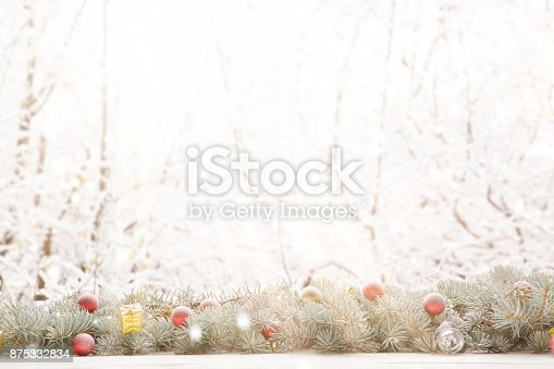 istock Christmas fir tree garland on wooden board on window sill over nature snowing tree park background with copy space 875332834