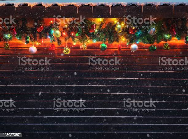 Photo of Christmas fir tree garland with Christmas tree decoration on wooden house wall. Bright Christmas and New Year background with empty space for text