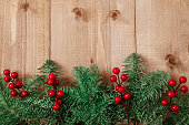 istock Christmas fir tree on wooden background. Red berries. 1061181558
