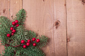 istock Christmas fir tree on wooden background. Red berries. 1061181560