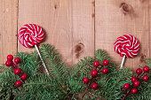 istock Christmas fir tree on wooden background. Red berries. 1061181614