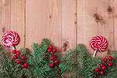 istock Christmas fir tree on wooden background. Red berries. 1061181616