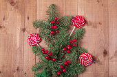 istock Christmas fir tree on wooden background. Red berries. 1061181626