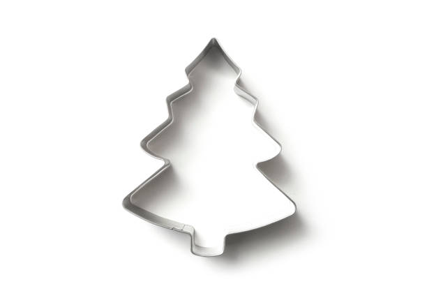 Christmas fir tree shape cookie cutter on white background closeup of Christmas fir tree shape cookie cutter on white background cookie cutter stock pictures, royalty-free photos & images