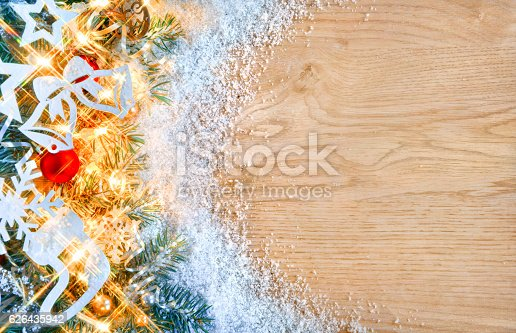 istock Christmas fir tree with lights and toys on wooden background. 626435942