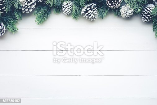 istock Christmas fir tree with pine branch decoration on white wood. 857789462