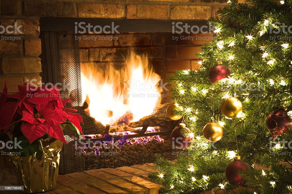 Christmas fire in fireplace, decorated tree, red poinsettia royalty-free stock photo