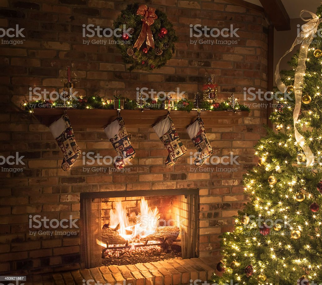 Christmas fireplace, quilted stockings, roaring fire, tree, lights, ornaments stock photo