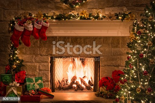 Christmas tree, gifts, stockings hanging from mantel by blazing fire in fireplace. Christmas eve.
