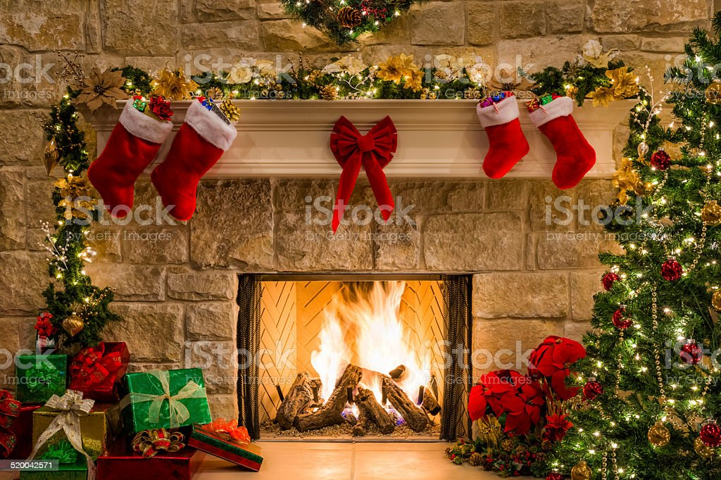 Christmas fireplace, tree, stockings, fire, hearth, lights, and decorations stock photo